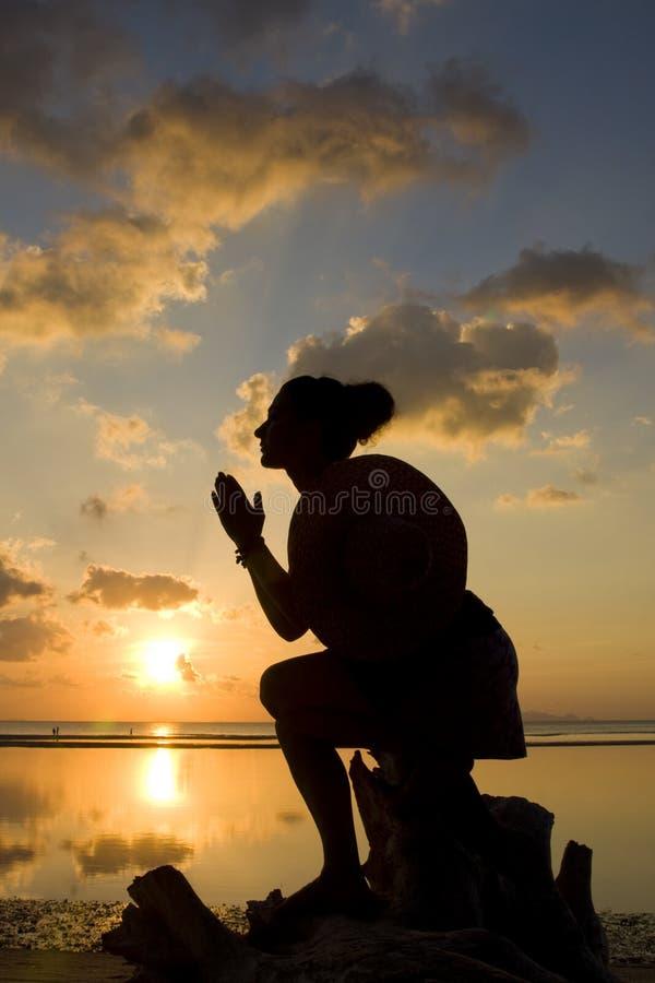 Siluetta della donna con le sue mani sollevate immagine stock