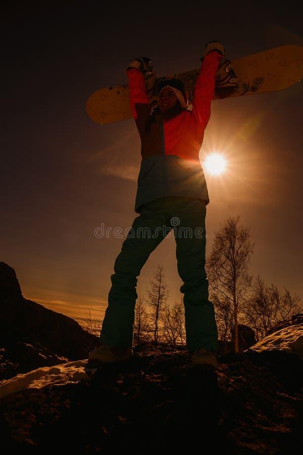 Siluetta della donna con lo snowboard al tramonto fotografia stock libera da diritti