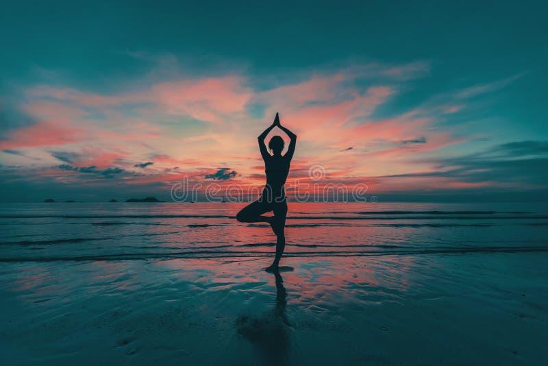 Siluetta della donna di yoga sulla costa di mare immagini stock