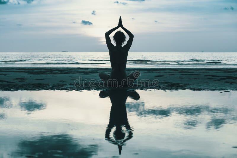 Siluetta della donna di yoga sulla costa di mare a penombra immagine stock libera da diritti