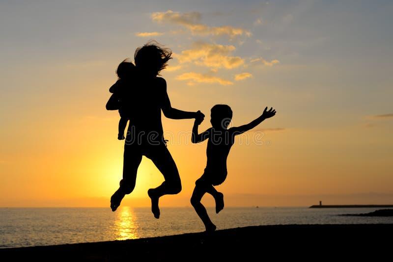Siluetta della donna emozionante con i bambini che hanno fotografie stock libere da diritti