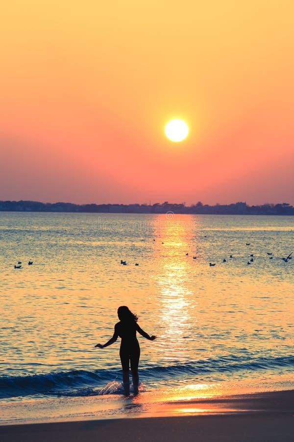 Siluetta della donna esile sulla spiaggia fotografia stock libera da diritti