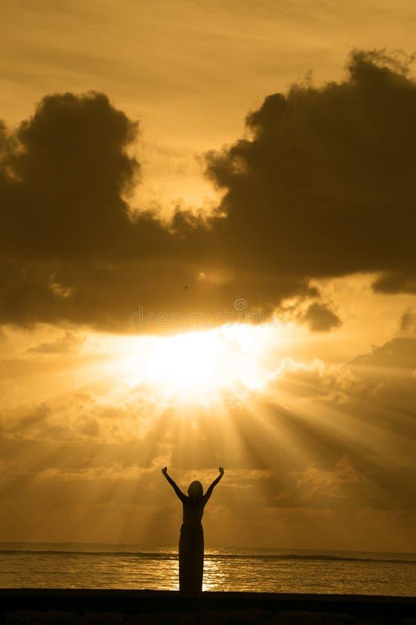Siluetta della donna felice ad alba fotografia stock
