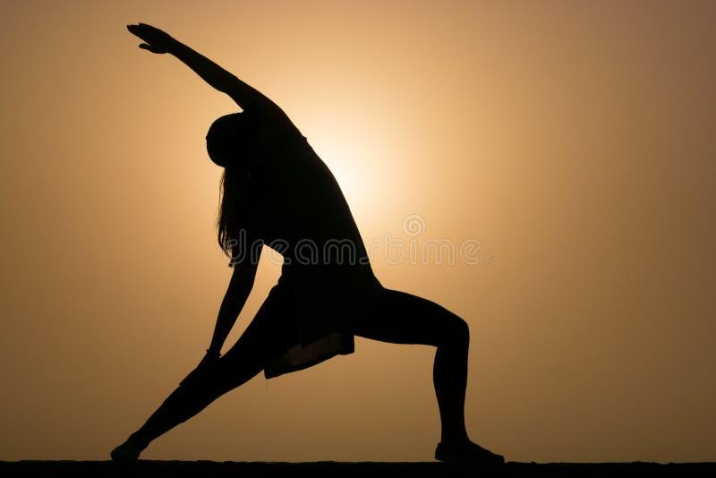 Siluetta della donna nella posa di yoga del guerriero tre immagine stock libera da diritti