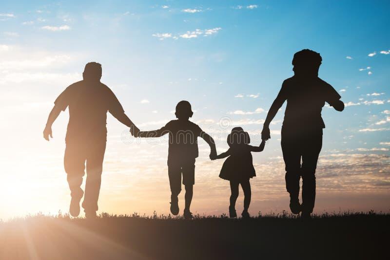 Siluetta della famiglia che mantene nel parco fotografie stock libere da diritti