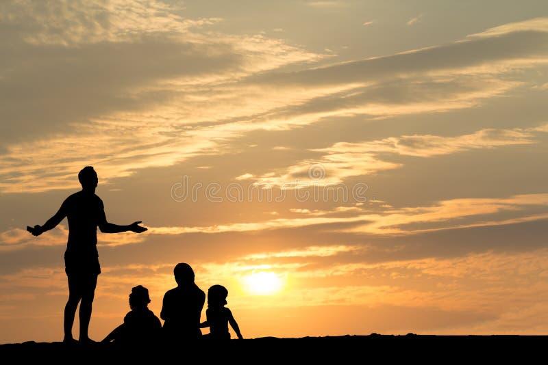 Siluetta della famiglia sulla spiaggia con il tramonto fotografia stock libera da diritti