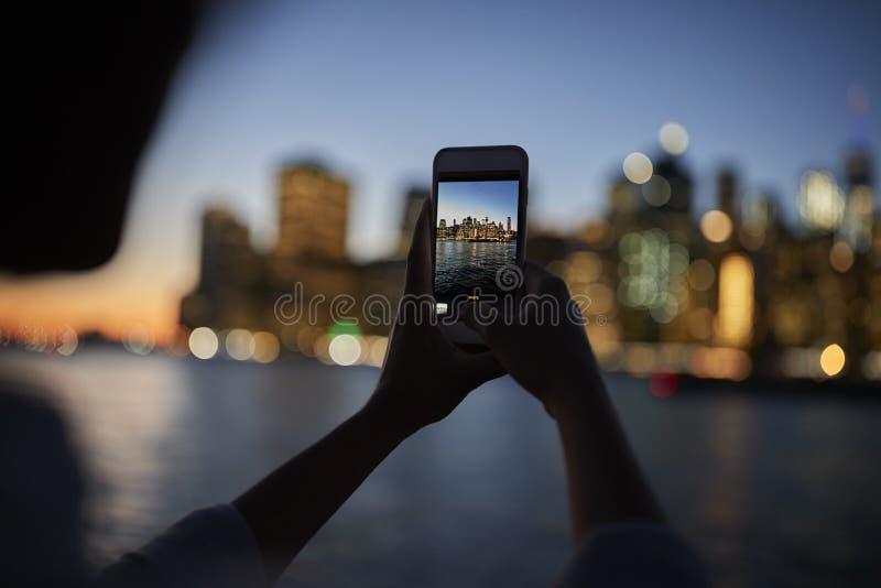Siluetta della foto di presa turistica dell'orizzonte di Manhattan al crepuscolo immagini stock libere da diritti