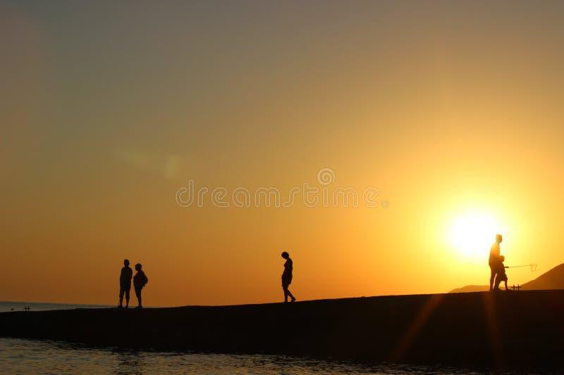 Siluetta della gente al sole, tramonto, siluette della gente sul pilastro, uguaglianti passeggiata fotografia stock libera da diritti