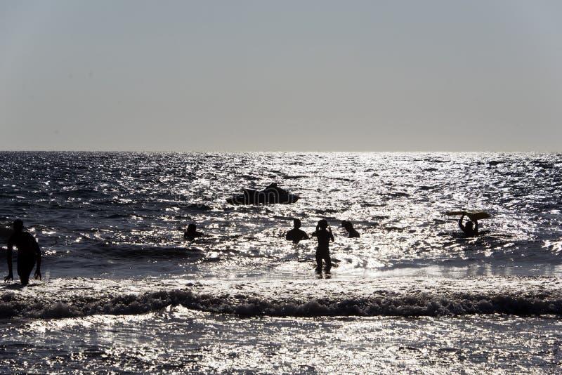Siluetta della gente che gioca, nuotante nelle onde nell'isola di Patmos, la Grecia nell'ora legale fotografia stock