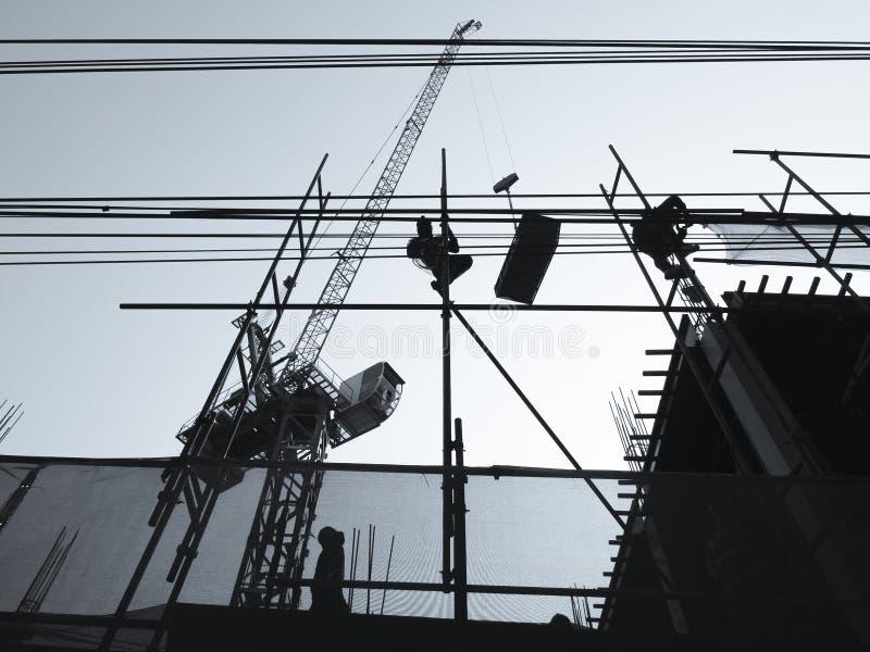 Siluetta della gente che lavora al fondo industriale del sito della costruzione di edifici immagini stock