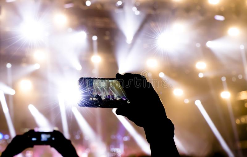 Siluetta della gente che spara l'evento di concerto con i telefoni cellulari fotografia stock libera da diritti