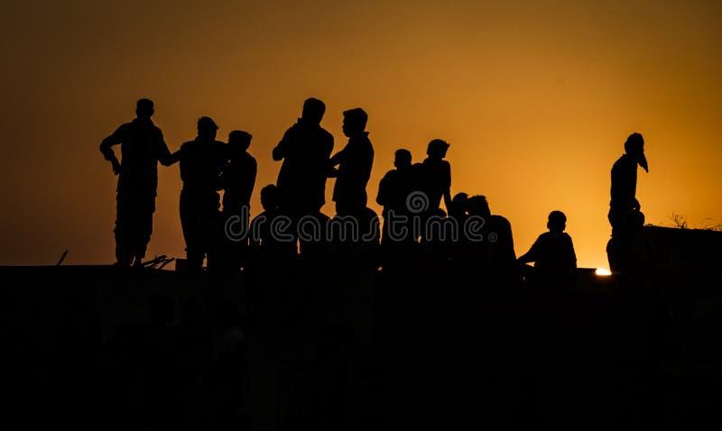 Siluetta della gente che sta sui festeggiamenti di sorveglianza del tetto qui sotto al tramonto immagine stock