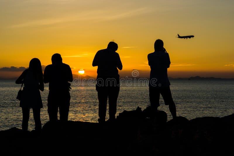 Siluetta della gente e dell'aeroplano durante il tramonto fotografia stock libera da diritti