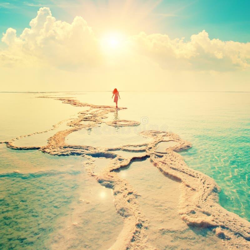 Siluetta della giovane donna che cammina sul mar Morto fotografie stock