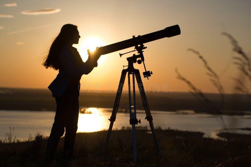 Siluetta della giovane donna che osserva vista tramite il telescopio il tramonto di estate immagini stock