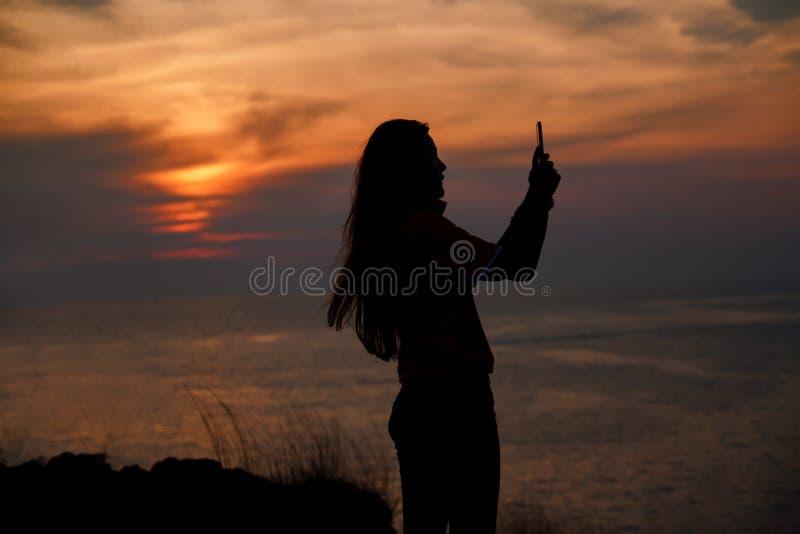 Siluetta della giovane donna che prende foto con la montagna ed il mare fotografia stock