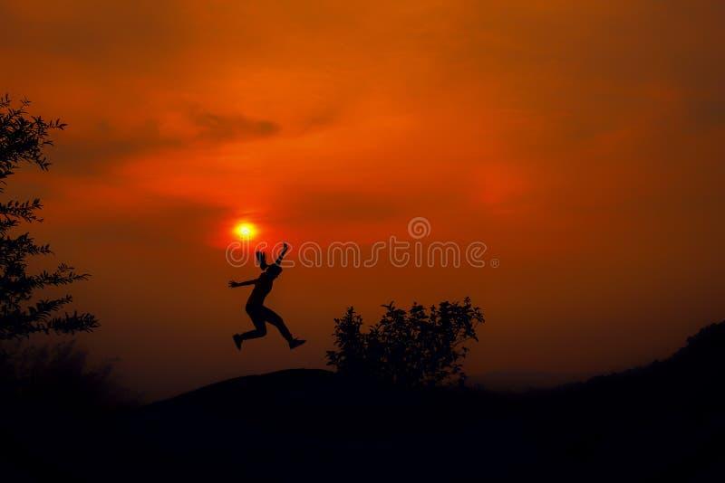 Siluetta della giovane donna che salta contro il tramonto con lo spazio della copia fotografia stock