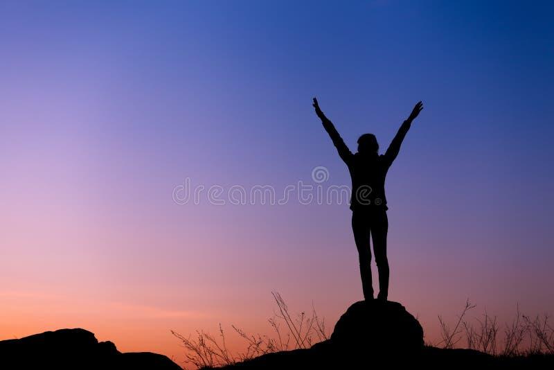 Siluetta della giovane donna felice contro il bello cielo variopinto fotografia stock libera da diritti