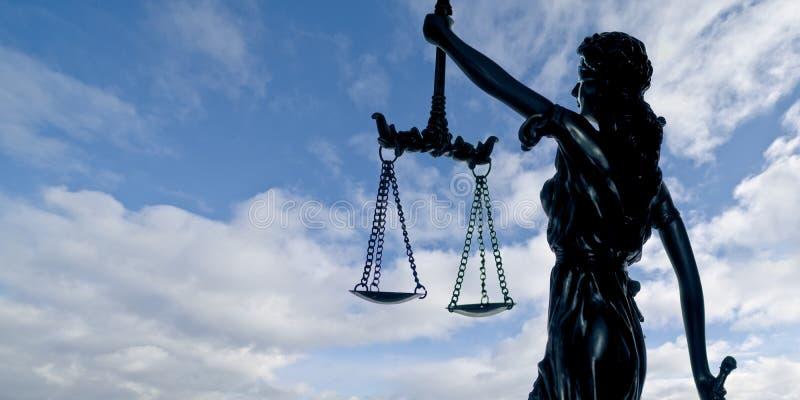 Siluetta della giustizia di signora contro un cielo drammatico immagine stock
