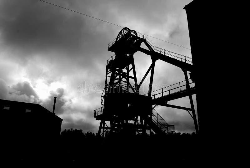 Siluetta della macchina di estrazione all'ingresso della miniera di estrazione mineraria immagini stock