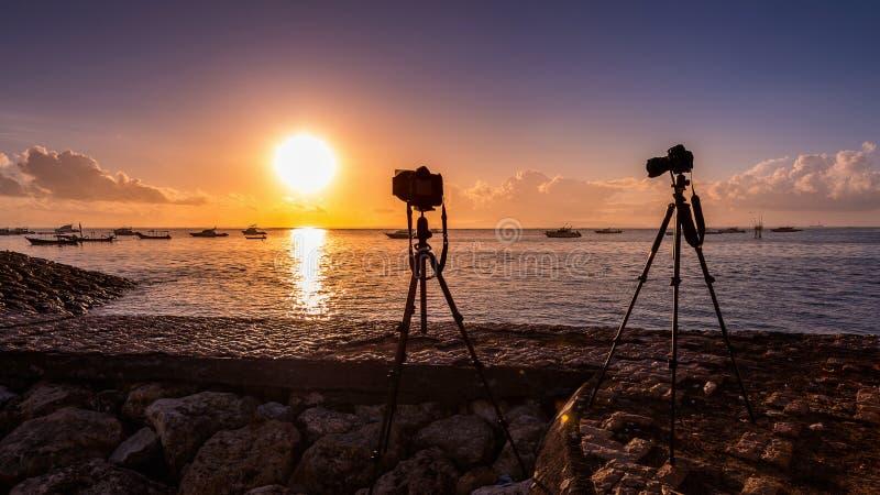 Siluetta della macchina fotografica sul mare della fucilazione del treppiede con il tramonto immagini stock