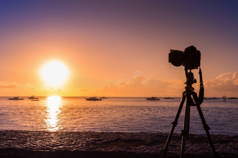 Siluetta della macchina fotografica sul mare della fucilazione del treppiede con il tramonto immagine stock libera da diritti