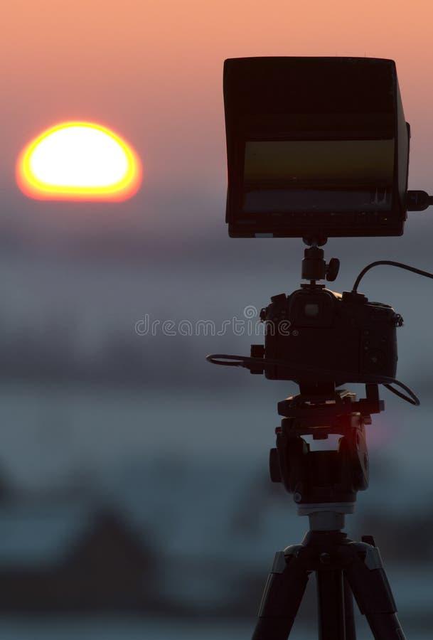 Siluetta della macchina fotografica sul treppiede che spara bella alba di inverno fotografia stock