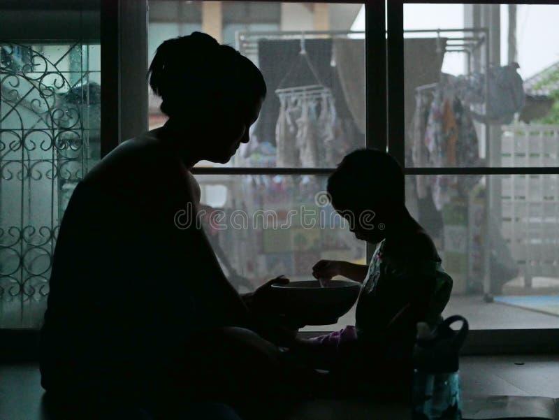 Siluetta della madre asiatica che tiene una ciotola di alimento per il suo bambino a casa fotografia stock libera da diritti