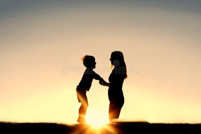 Siluetta della madre e del bambino piccolo che si tengono per mano al tramonto immagine stock