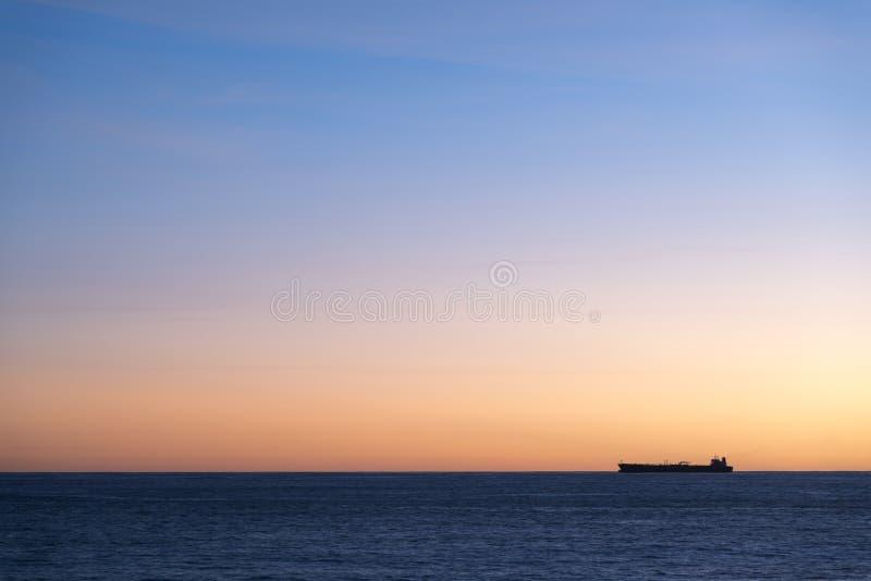 Siluetta della nave da carico sull'orizzonte fotografia stock libera da diritti
