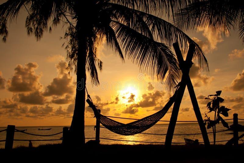 Siluetta della palma e del hammock fotografia stock