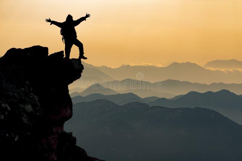 Siluetta della persona sul picco di montagna fotografia stock libera da diritti