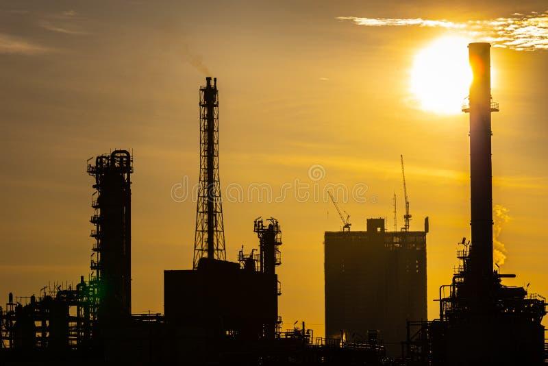 Siluetta della pianta di industria della raffineria del gas e del petrolio con illuminazione ed alba di scintillio di mattina, immagini stock libere da diritti
