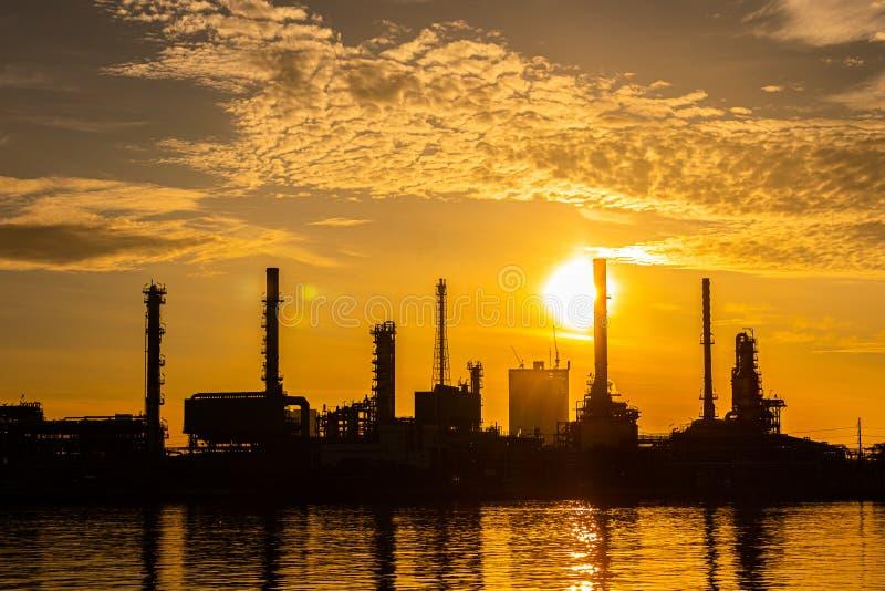 Siluetta della pianta di industria della raffineria del gas e del petrolio con illuminazione ed alba di scintillio di mattina, fotografie stock