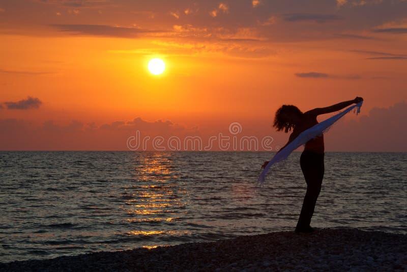 Siluetta della ragazza con il fazzoletto al tramonto fotografia stock libera da diritti