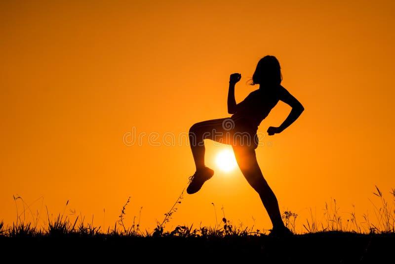 Siluetta della ragazza di kick boxing che esercita scossa fotografie stock libere da diritti