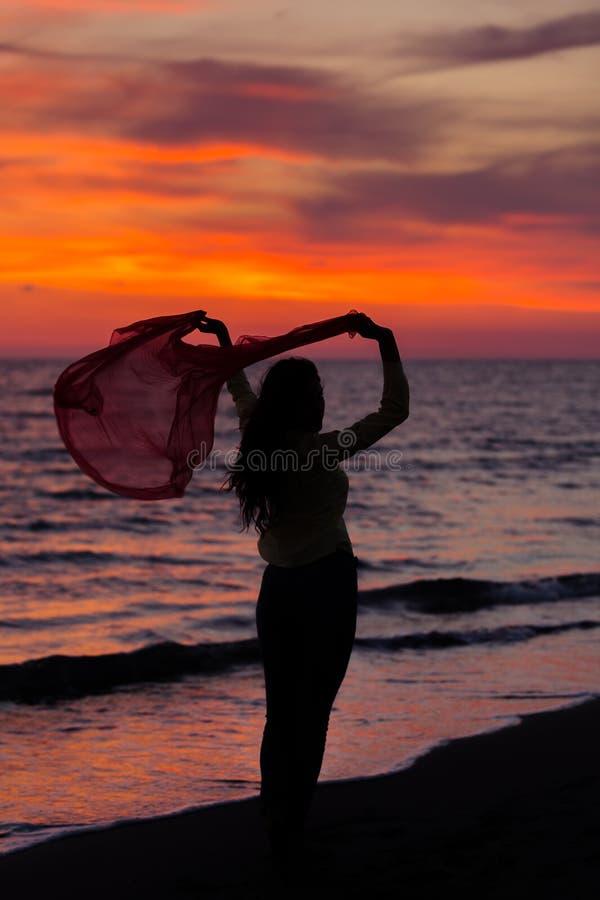 Siluetta della ragazza, saltante con il panno di seta contro del tramonto del mare fotografie stock