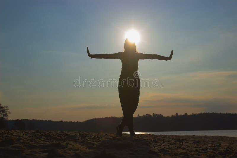 Siluetta della ragazza in vestiti neri che ballano, alla riva del fiume fotografie stock libere da diritti