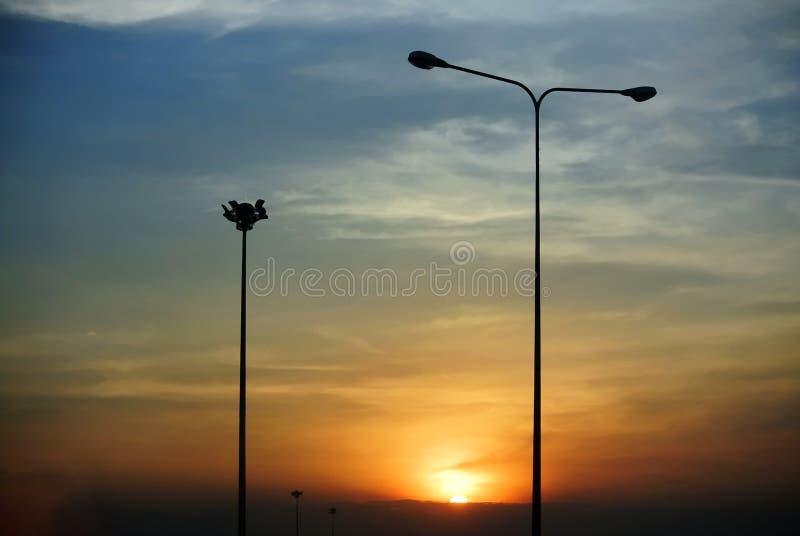 Siluetta delle colonne di illuminazione di via durante il tramonto fotografia stock