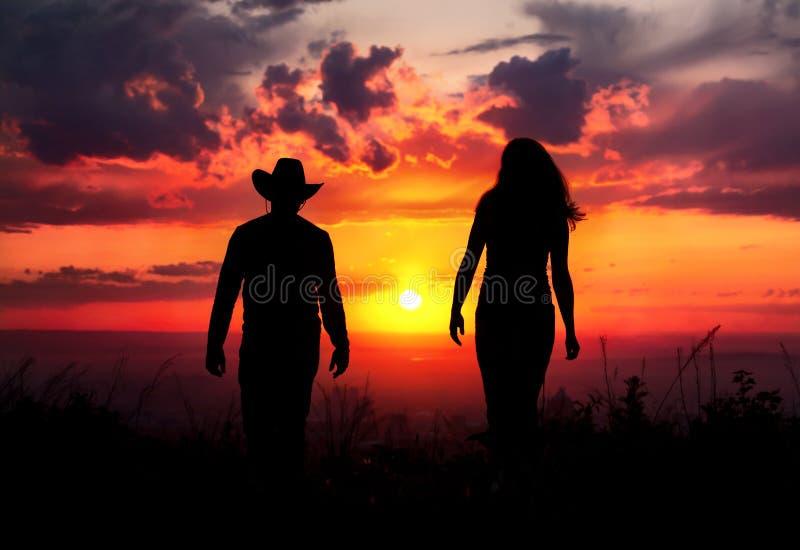 Siluetta delle coppie del cowboy al tramonto fotografia stock libera da diritti