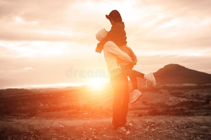 Siluetta delle coppie felici alla nebbia ed al sole scenici della montagna fotografia stock libera da diritti