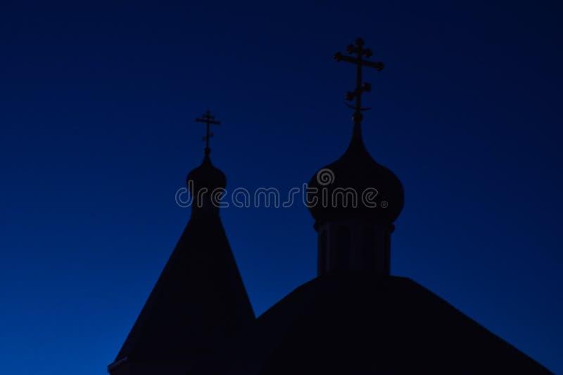 Siluetta delle cupole con gli incroci della chiesa ortodossa contro il cielo blu nella sera fotografie stock