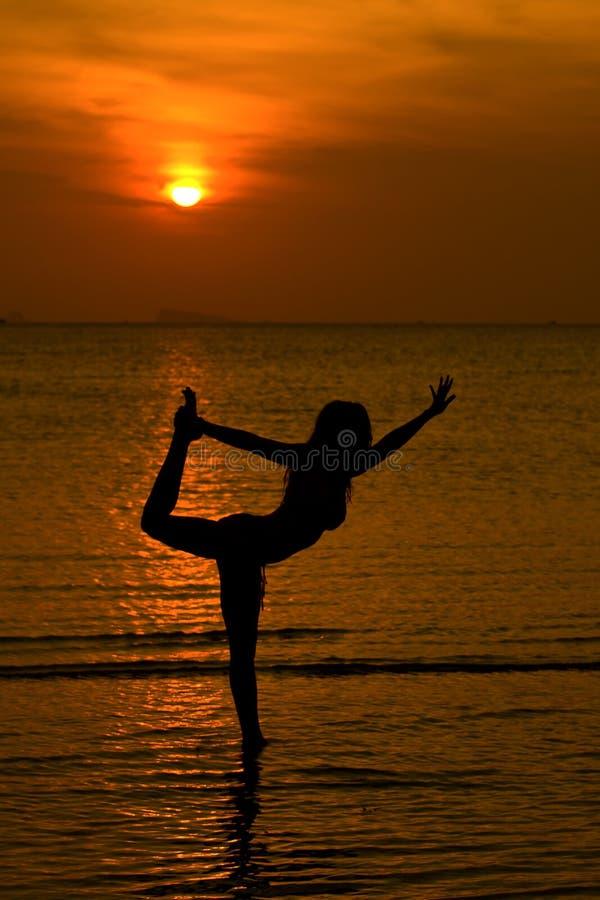 Siluetta delle donne di yoga al tramonto fotografia stock