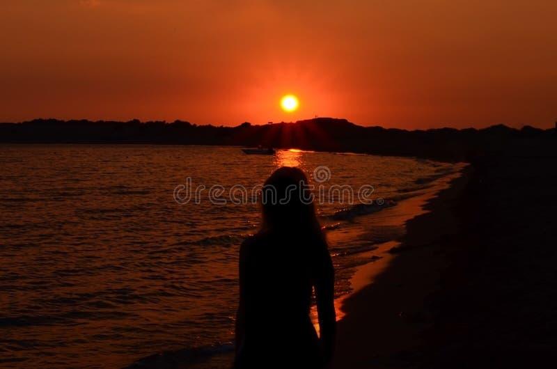 Siluetta delle donne sulla spiaggia contro il cielo durante il tramonto fotografie stock libere da diritti