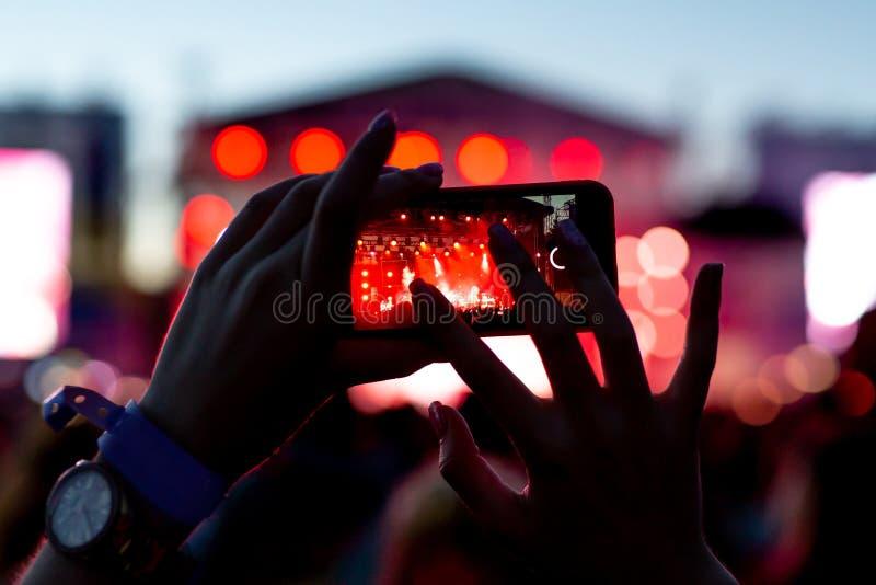 Siluetta delle mani con uno smartphone ad un grande festival di musica immagini stock