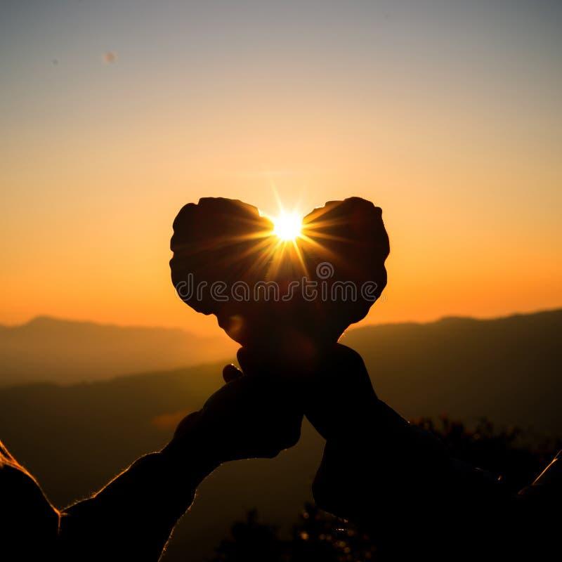 Siluetta delle mani delle coppie che tengono forma del cuore ai precedenti di tramonto del cielo fotografia stock