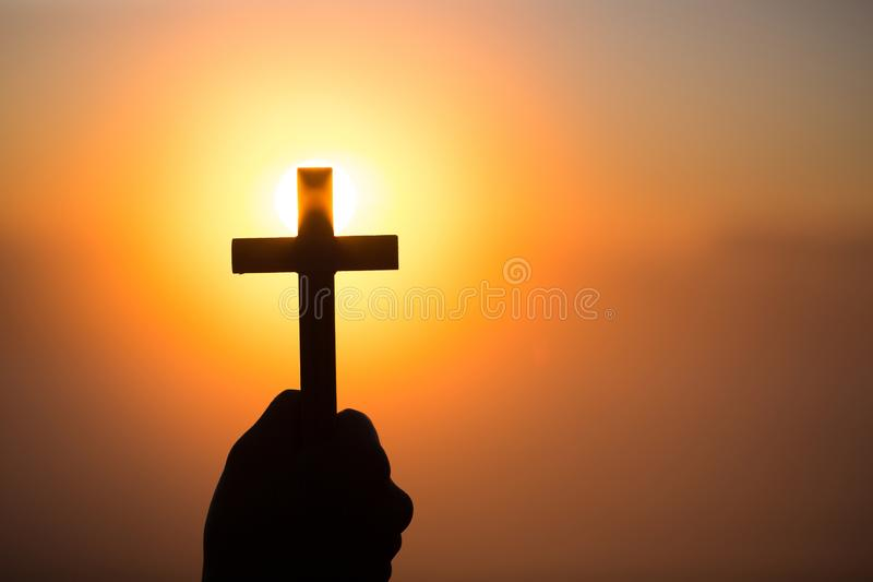 Siluetta delle mani della donna che pregano con l'incrocio nel fondo di alba della natura, croce, simbolo di fede Crisi cristiana immagini stock
