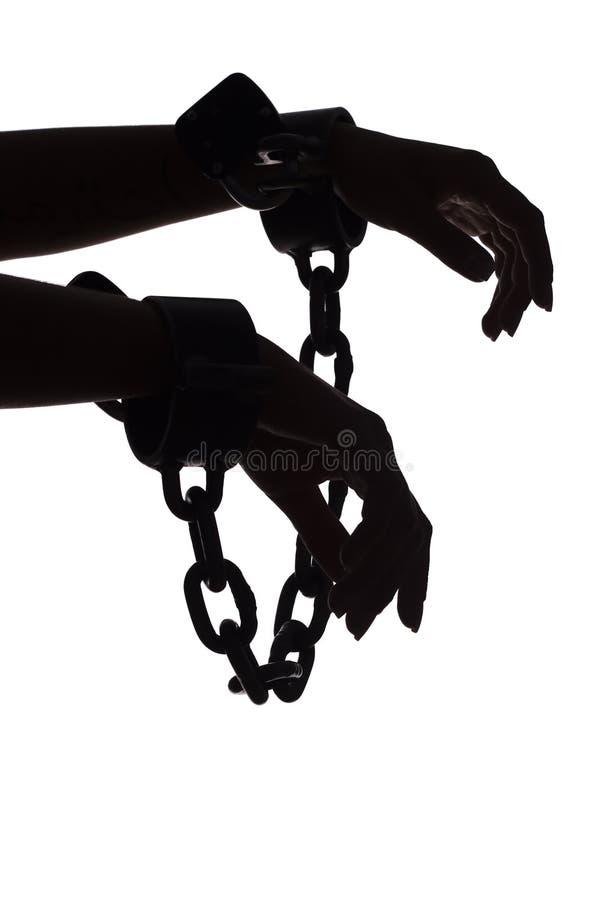 Siluetta delle mani della donna con le catene immagine stock libera da diritti