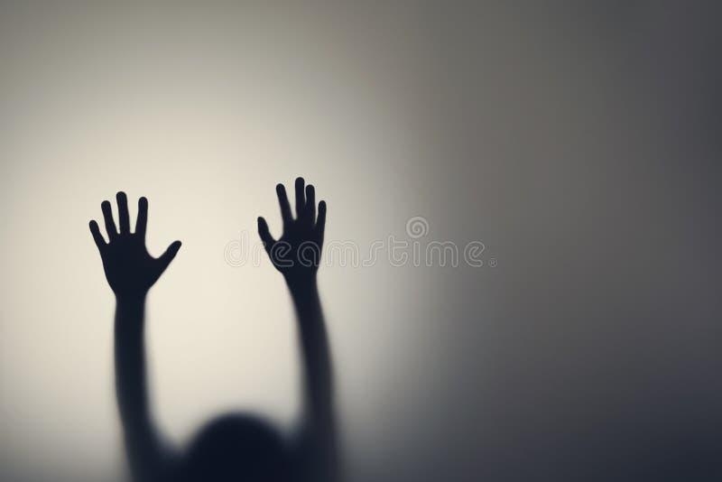 Siluetta delle mani della donna dietro la porta di vetro Concetto della depressione, timore, attacchi di panico immagine stock libera da diritti