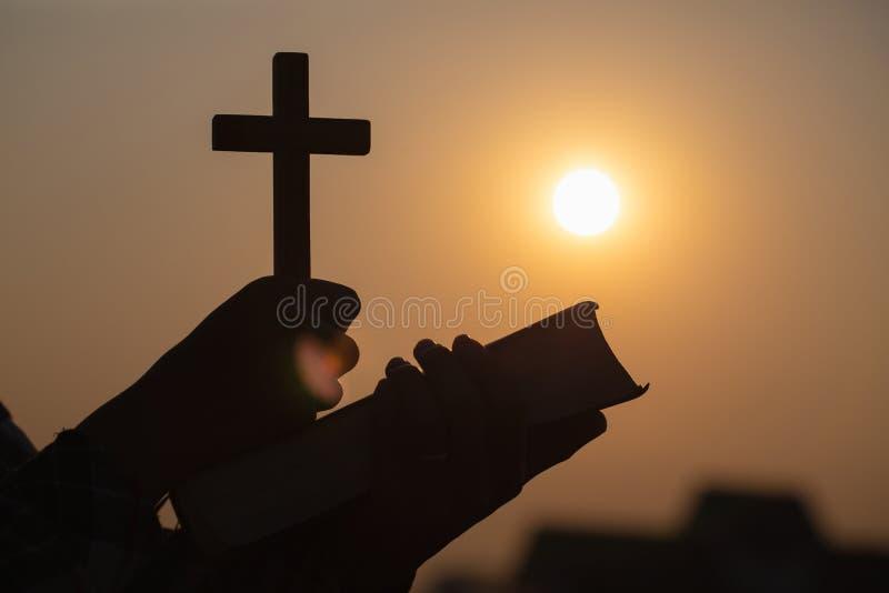 Siluetta delle mani della giovane donna che tengono bibbia santa e ascensore dell'incrocio cristiano, del simbolo di religione al fotografia stock libera da diritti